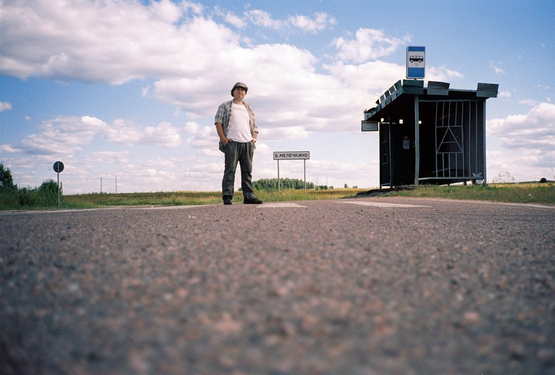 мужчина сфотографирован на фоне автобусной остановки яркого неба и надписи барское-мелечикно