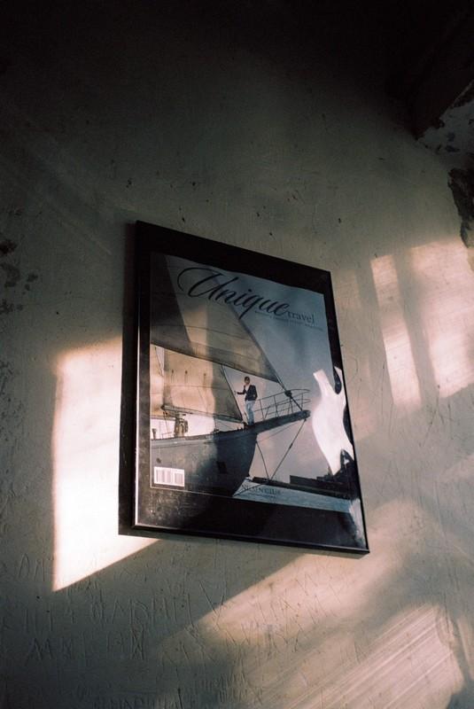 плакат на стене с изображением человека на яхте в деревенском доме