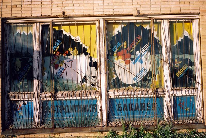 вывеска бакалейно-гастрономического магазина позднего советского периода. решетки на окнах и надписи молоко, яйцо, рыба, хлеб, фрукты, соки