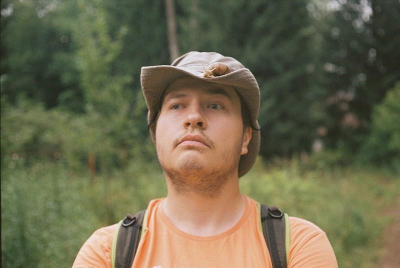 Большая улитка сидит на шляпе мужчины в оранжевой футболке