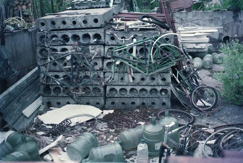 множество старых советских велосипедов подвешены на бетонные плиты, вокруг куча пустых бутылей для воды