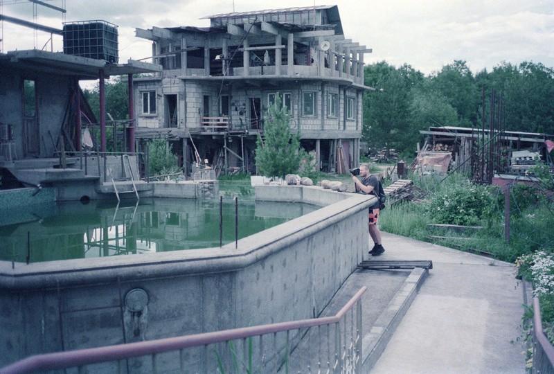 Дачный бассейн из бетона, на заднем фоне трех этажный дом из бетона. Мужчина с Bronica фотографирует бассейн