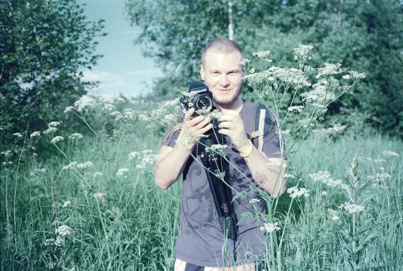 Кирилл с фотоаппаратом Bronica и штативом стоит в зеленой траве по пояс
