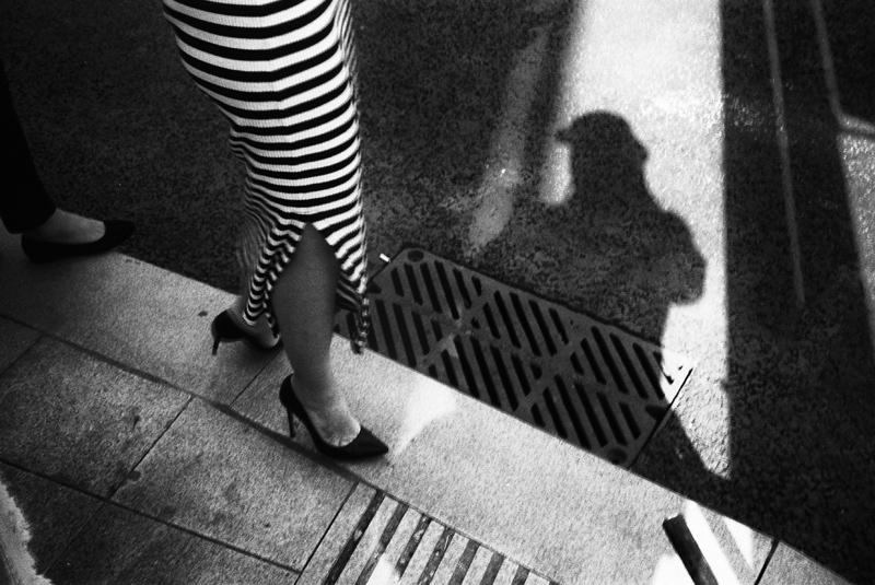 девушка в платье переходит дорогу в тени фотографа