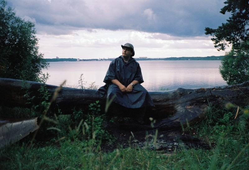 Мужчина в плаще сидит на дереве под дождем на озере Сенеж