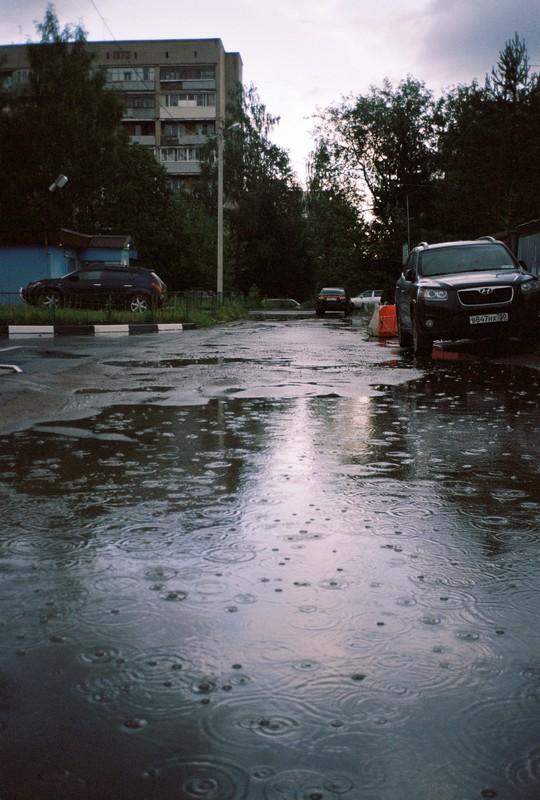 Капли дождя бьют по асфальту и лужам в Тимоново