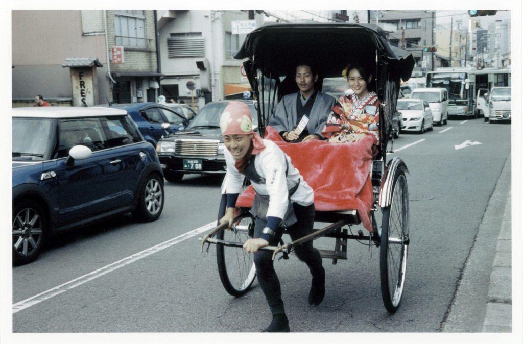 Японская пара катается на бегорикше в районе Асакуса, Токио