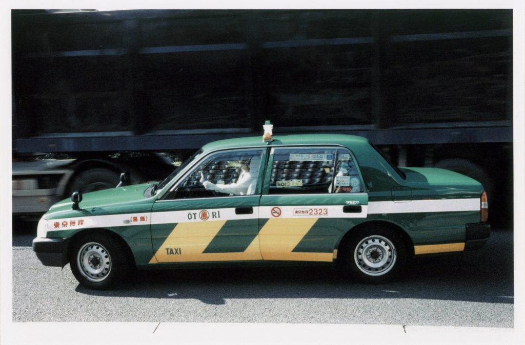 Зеленое такси на городском шоссе на фоне черного грузовика, Токио