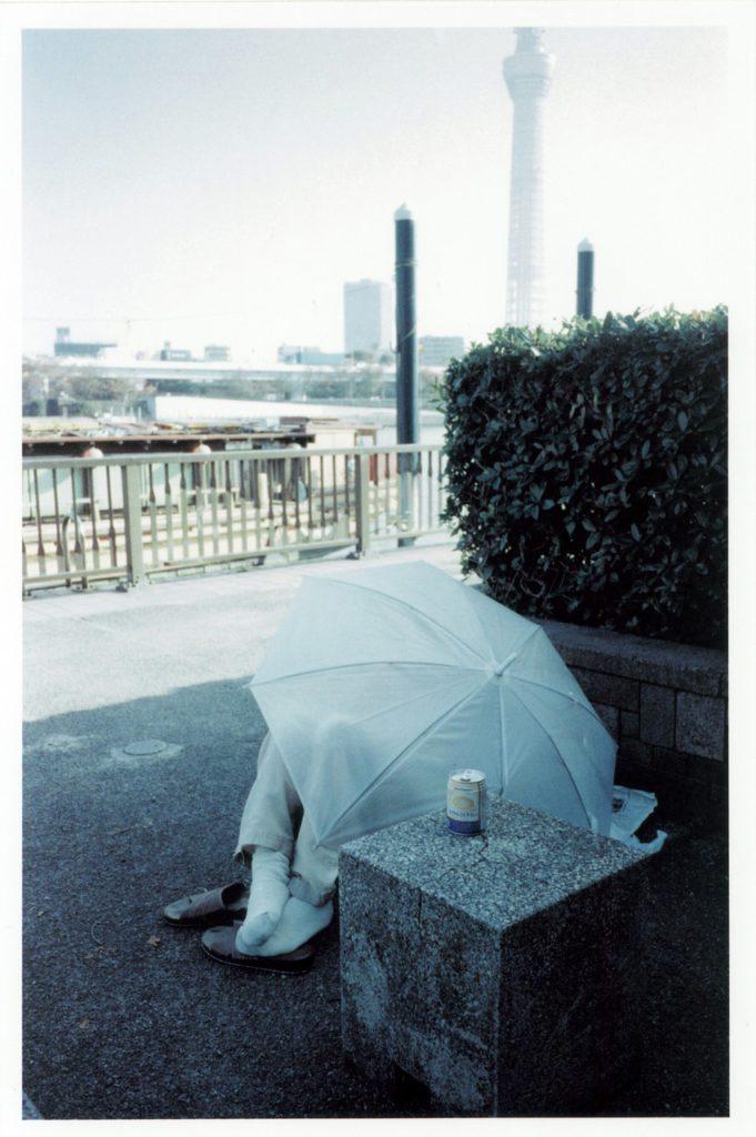 Неизвестный отдыхает под белым зонтом на правом берегу реки Сумида, Токио