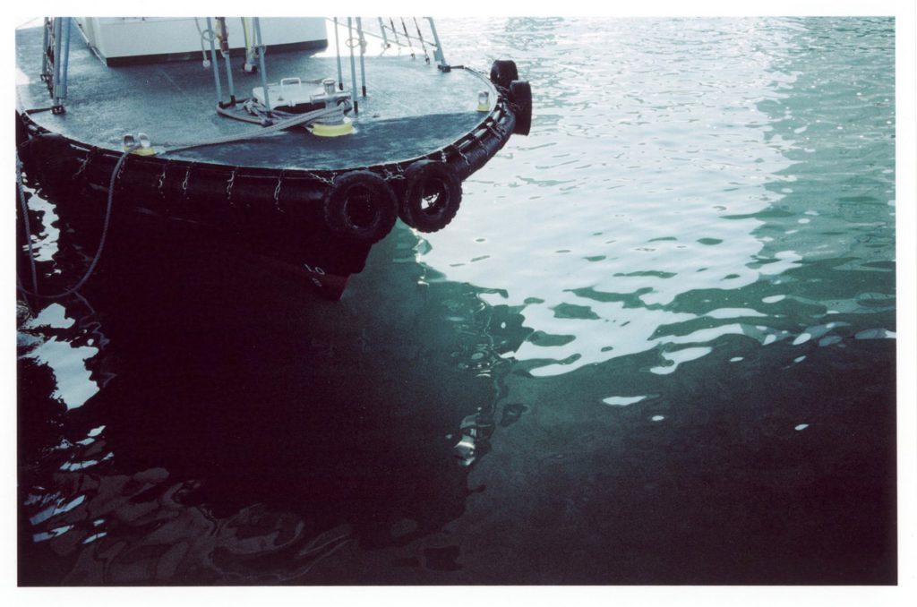 Зеленая вода и рыболовецкое судно в порте города Кобе