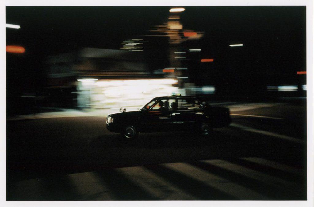 Черное такси ночью на улицах Осаки