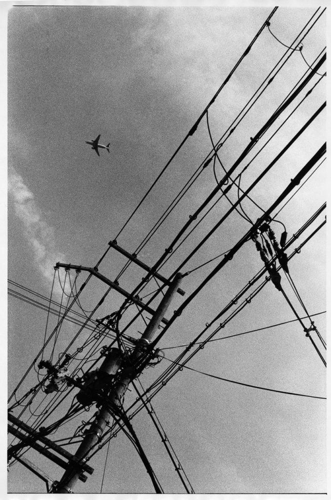 Самолет из Итами пролетает над линиями электропередач
