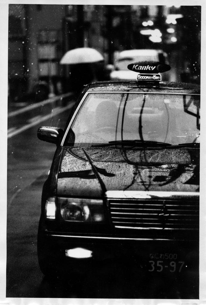 Капли дождя на японском такси черного цвета в Осаке
