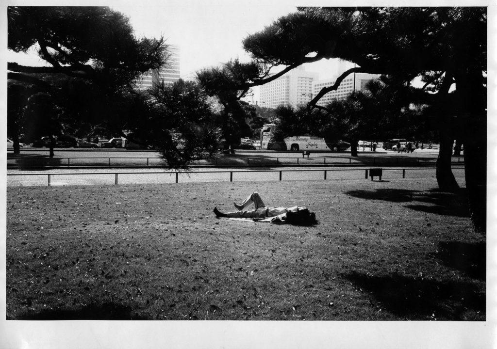 Японский рабочий отдыхает в парке рядом с дворцом императора, Токио