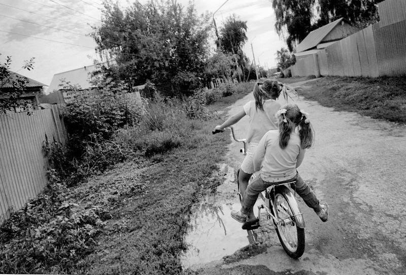 Девочки едят на велосипеде в городе Димитровград