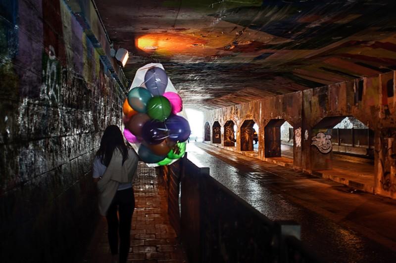 Девушка с воздушными шариками в подземном переходе