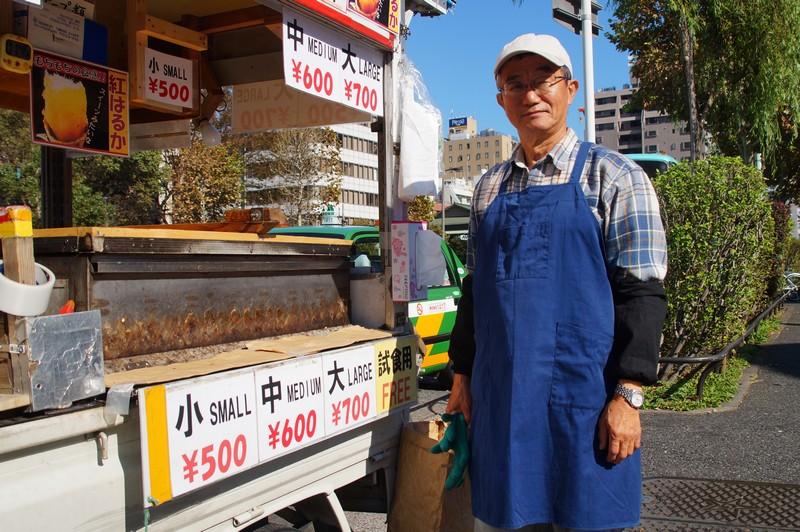 продавец жареного на камнях сладкого картофеля