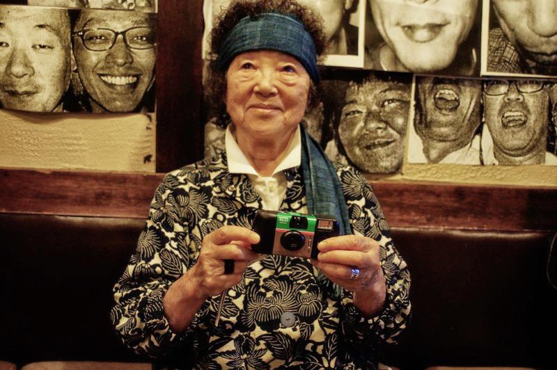 Портрет Мичико Сасаки - 84 летнего фотографа. В руках одноразовая мыльница Fujifilm.