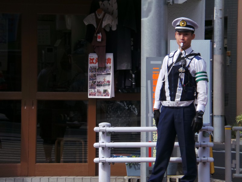 Молодой регулировщик движения на улицах Токио
