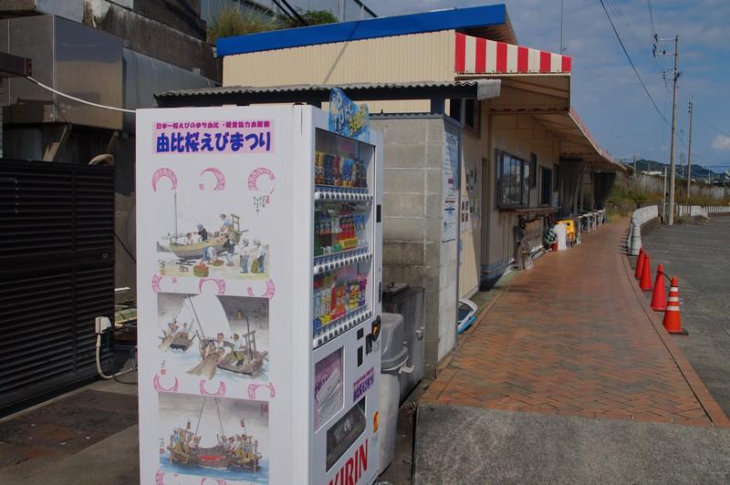 Вид на портовое кафе с автоматом с плакатом о фестивале креветок Эби города Юи
