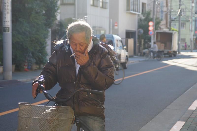 Малоимущий японец курит сигарету во время езды на велосипеде