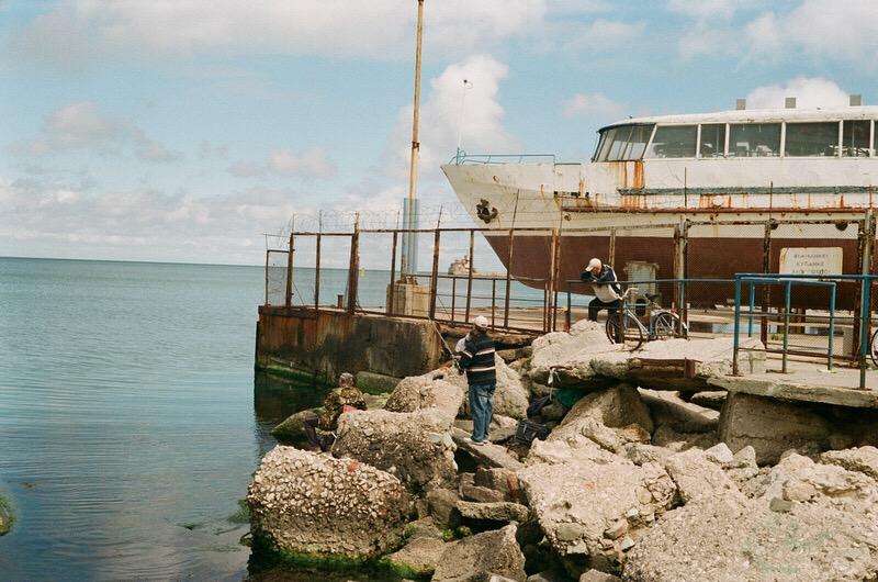 Феодосия. Рыбаки на пристани на фоне корабля.